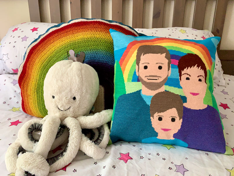 a handmade tapestry cushion on a bed. The image on the cushion is a stylised family portrait in front of a rainbow.